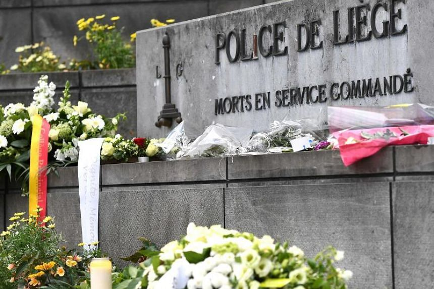 Flowers laid in front of Liege police headquarters in tribute to victims of a shooting in Liege.