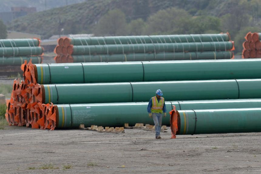 A workman walks past steel pipe to be used in the oil pipeline construction of Kinder Morgan Canada's Trans Mountain Expansion Project at a stockpile site in Kamloops, British Columbia, Canada, on May 29, 2018.