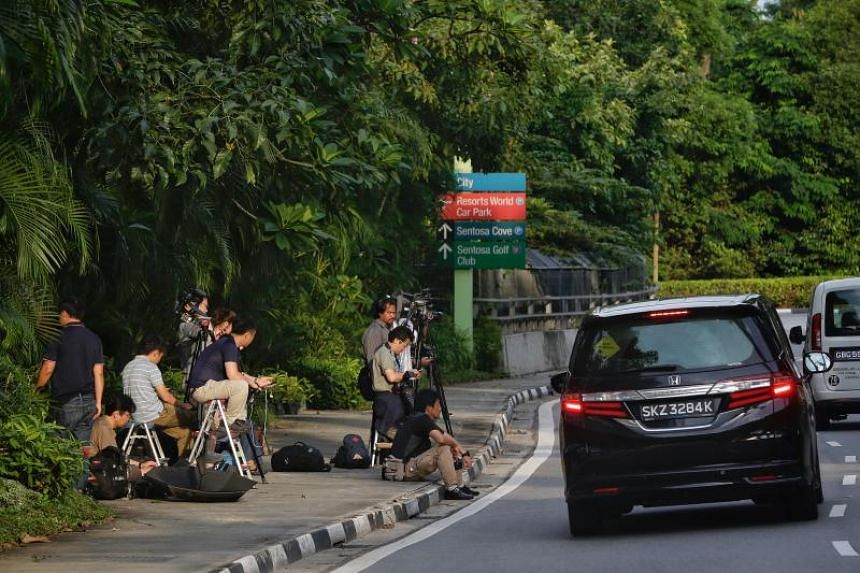 The media wait opposite the entrance of a road that leads to Capella Hotel on May 30, 2018.
