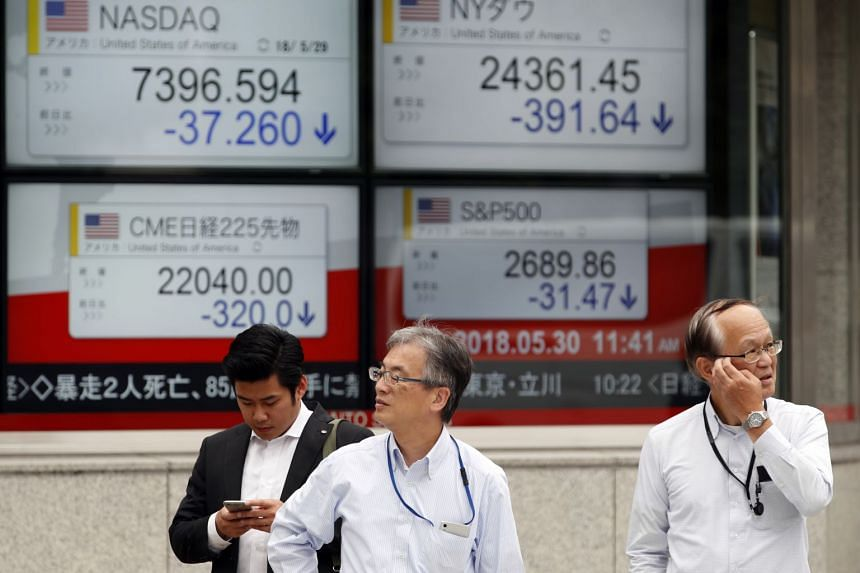 Pedestrians stand before a stock market indicator board in Tokyo, Japan, on May 30, 2018