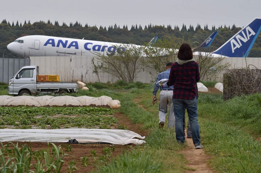 Farmers working on a farm beside the expanding Narita airport, Tokyo's main international gateway, in Chiba prefecture, on April 12, 2018.