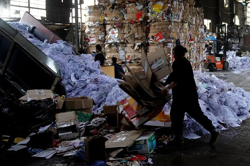 Labourers work at a paper products recycling station in Shanghai, China.