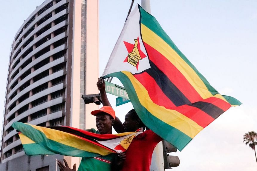 People holding Zimbabwean flags celebrate in the streets of Harare after the resignation of Zimbabwe's president Robert Mugabe on Nov 21, 2017.