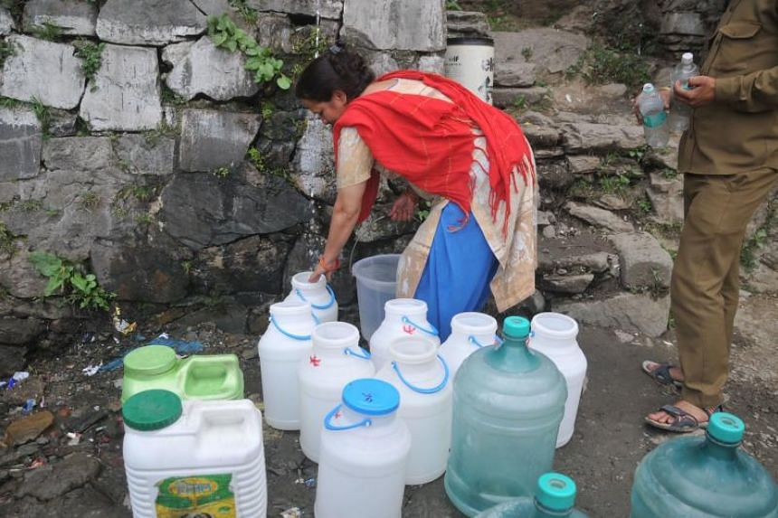 Indian residents in Shimla waiting to collect drinking water as the city faces water shortage.