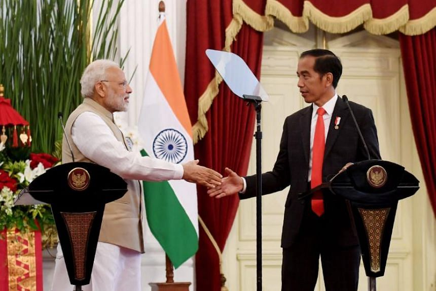 Indonesia's President Joko Widodo (right) shakes hands with India's Prime Minister Narendra Modi during a joint press conference at the presidential palace in Jakarta, on May 30, 2018.