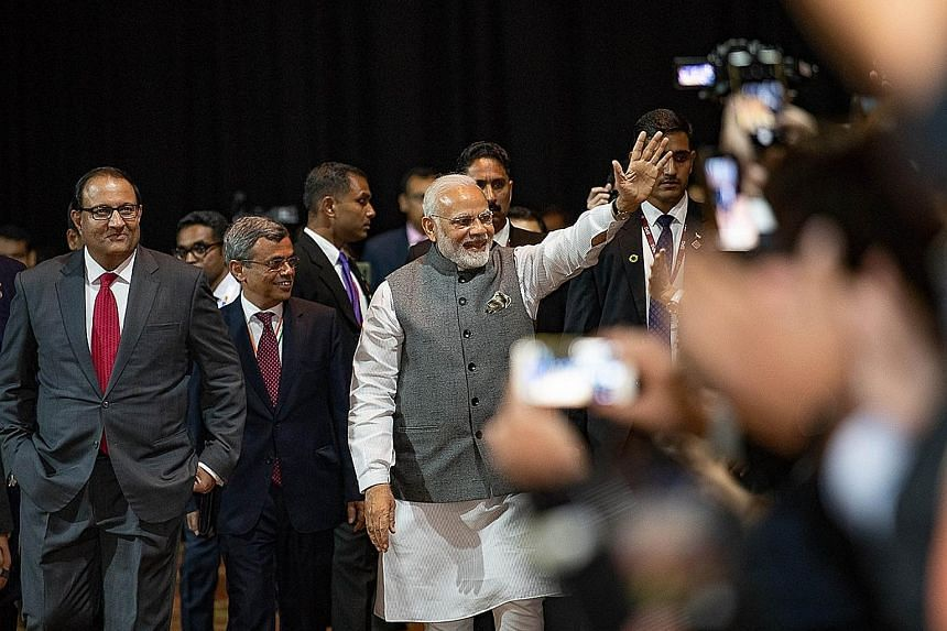 Visiting Indian Prime Minister Narendra Modi waving to businessmen at a Singapore-India business event at the Marina Bay Sands Convention Centre yesterday. With him are Minister-in-charge of Trade Relations S. Iswaran (far left) and India's High Comm