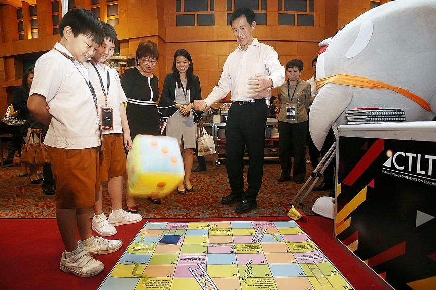 Education Minister Ong Ye Kung throwing a dice as he played a game of snakes and ladders focused on the theme of cyber wellness, created by Ahmad Ibrahim Primary School pupils Austin Kho (left) and Loo You En (second from left), and their teachers. W