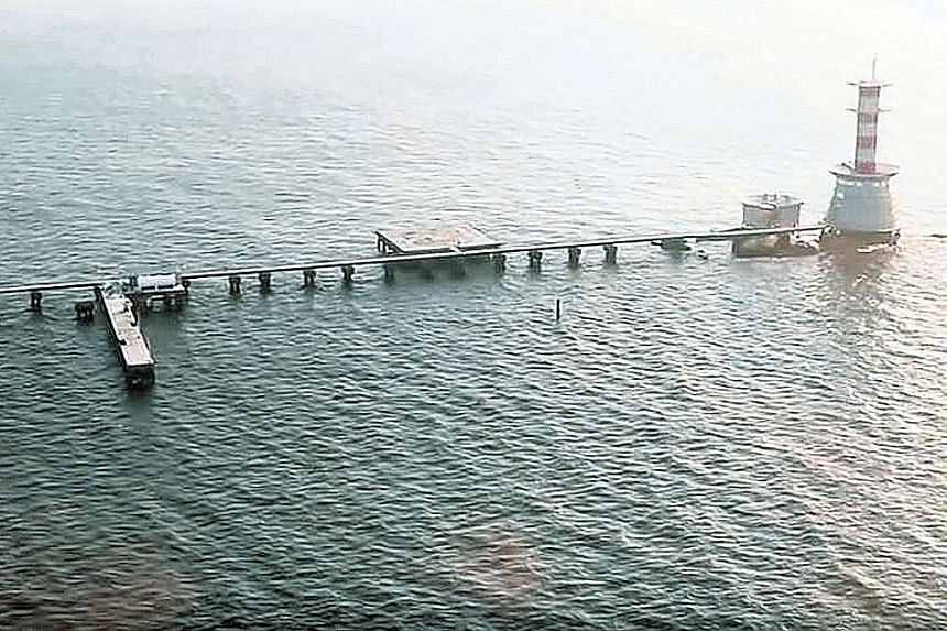 A 2008 judgment by the International Court of Justice awarded sovereignty of Pedra Branca (background) to Singapore. The court awarded Middle Rocks (foreground) to Malaysia, but it did not make a definitive ruling on South Ledge, saying it belongs to