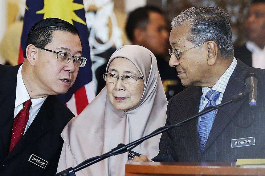 From left: Malaysian Finance Minister Lim Guan Eng, Deputy Prime Minister Wan Azizah Wan Ismail and Prime Minister Mahathir Mohamad at a press conference in Putrajaya on Wednesday.