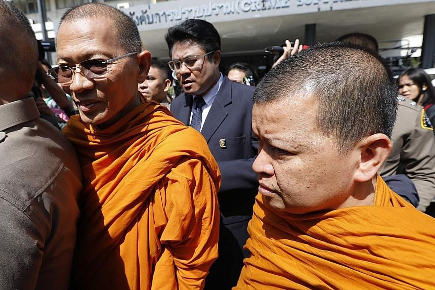 Buddhist monks Phra Promdilok (left) and Phra Attakitsophon leaving the Police Crime Suppression Division in Bangkok after questioning last week.