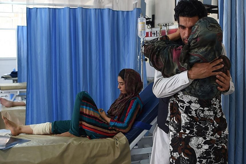A wounded Afghan girl and her weeping relatives at Wazir Akbar Khan hospital after a gun and bomb attack on the Interior Ministry in Kabul on Wednesday.