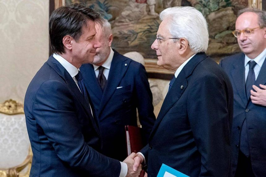 Newly appointed Italian Prime Minister Giuseppe Conte (left) shaking hands with Italy President Sergio Mattarella after signing the list of the new cabinet on May 31, 2018.