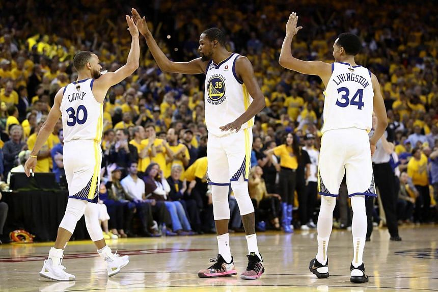 Stephen Curry #30 of the Golden State Warriors celebrates with Kevin Durant #35 and Shaun Livingston #34 against the Cleveland Cavaliers on May 31, 2018.