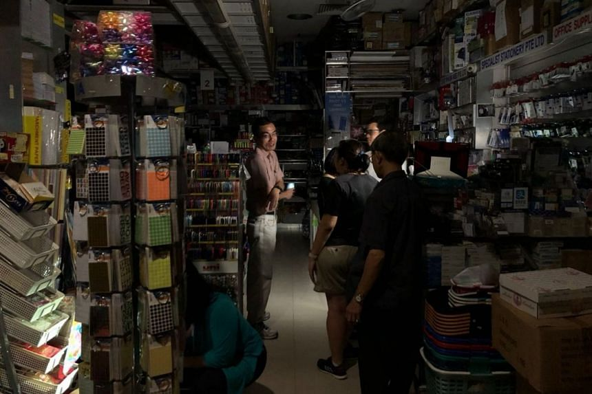 Shop owners were seen standing along the corridor in the dark at The Arcade in Raffles Place after the massive blackout.