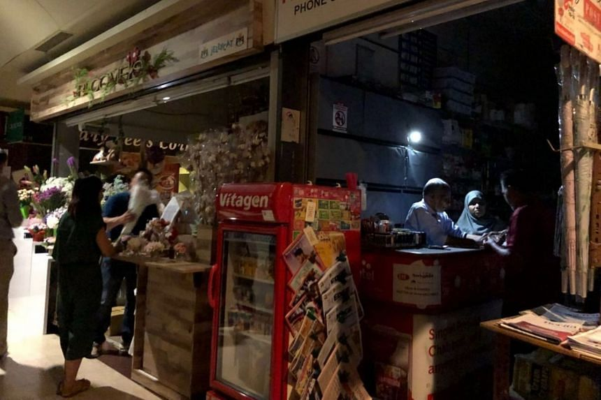 Shop owners working in the dark during the blackout at The Arcade in Raffles Place.