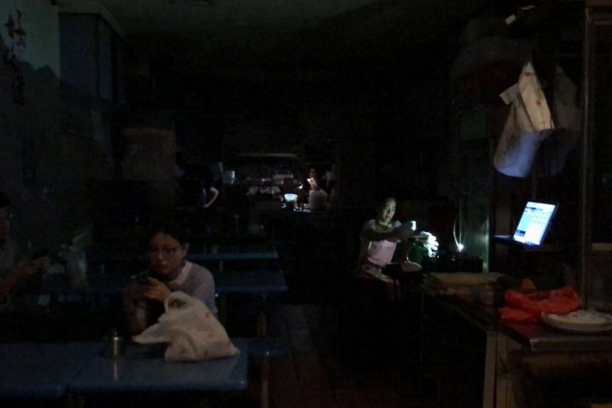 People at a food stall at The Arcade in Raffles Place during a massive blackout on the afternoon of June 1, 2018.