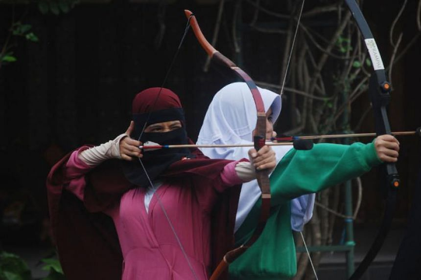 Indonesian Muslim women practising archery while waiting to break their fast in Bandung in May, 2018. Some people prefer exercising just before they can start eating.