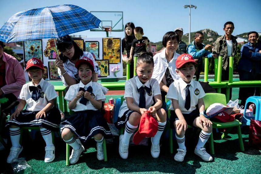 Parents and their children attend an event at a village square on International Children's Day on Gouqi Island in Zhejiang province, China, on June 1, 2018.