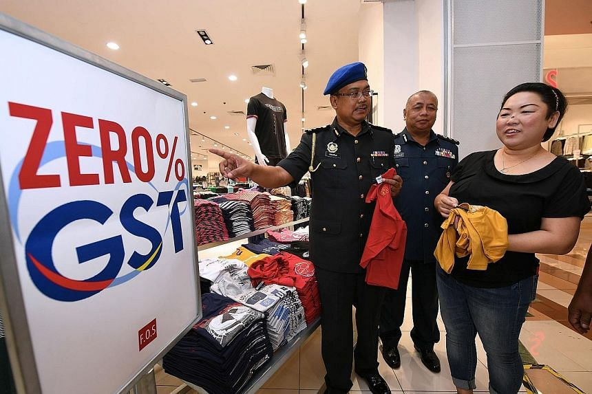 Officers from the Domestic Trade, Cooperatives and Consumerism Ministry in Johor state checking on a business outlet yesterday. Malaysia's unpopular 6 per cent GST was zero rated by the new Mahathir Mohamad administration to fulfil an election promis