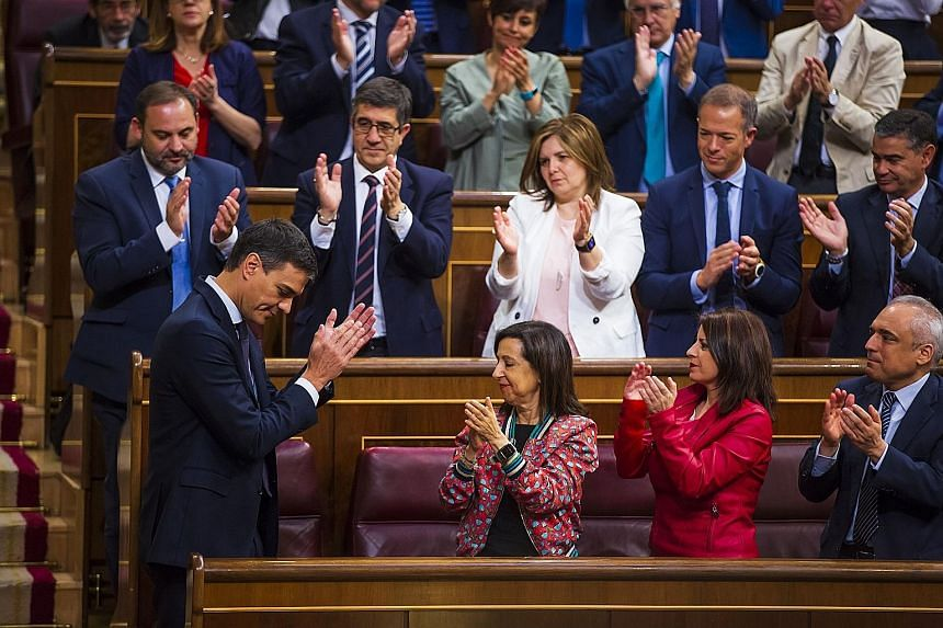 Mr Pedro Sanchez (left) acknowledging the applause of his Spanish Socialist Party yesterday as he became Spain's latest Prime Minister.