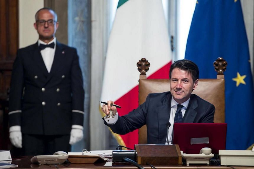 Newly appointed Italian Prime Minister Giuseppe Conte (right) rings the small silver bell to open the first council of Ministers at Chigi Palace in Rome, on June 1, 2018.