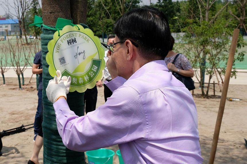 Finance Minister Heng Swee Keat signs on a plaque of the beech tree he helped plant at the Singapore-Nanjing Eco Hi-Tech Island on June 2, 2018.