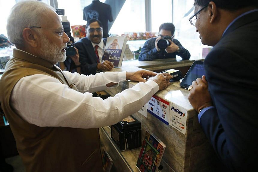 India Prime Minister Narendra Modi using his RuPay contactless card to pay for a souvenir at the Indian Heritage Centre on June 2, 2018.