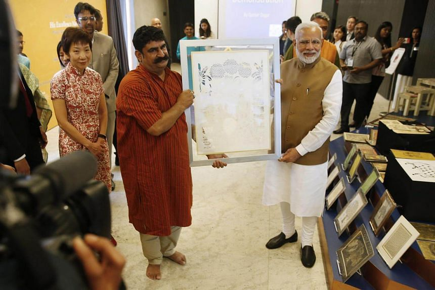India Prime Minister Narendra Modi is presented with an artwork by one of the craftsmen from Kala Sangam, a cultural platform launched by Mr Modi at the Indian Heritage Centre on June 2, 2018.