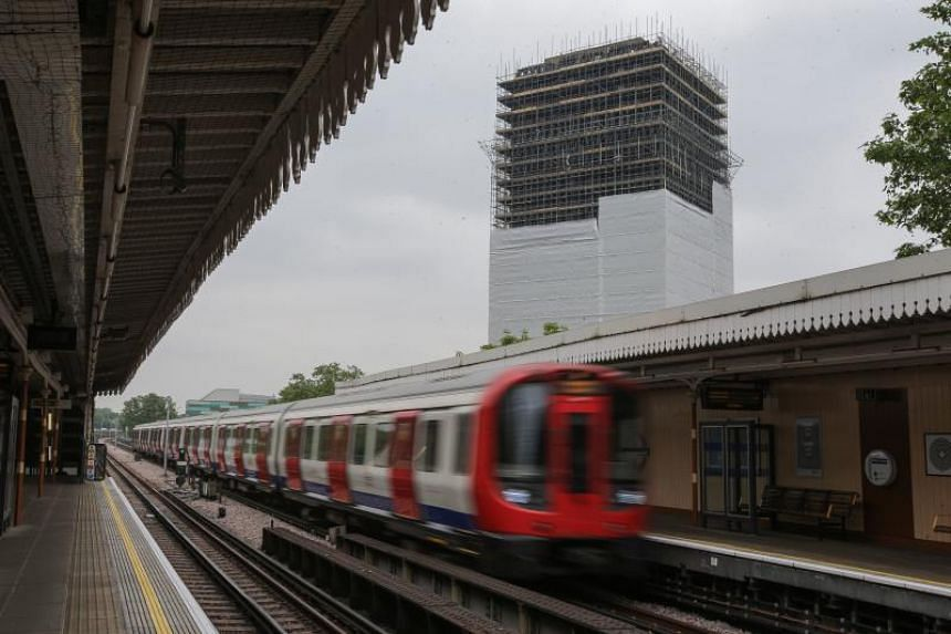 A tube train passes through Latimer Road station near the burned-out shell of Grenfell Tower block in west London on May 25, 2018.