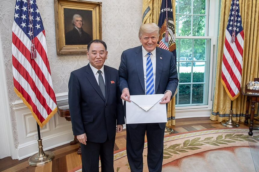 US President Donald Trump is presented with a letter from North Korean leader Kim Jong Un by North Korean envoy Kim Yong Chol in the Oval Office at the White House in Washington on June 1, 2018.