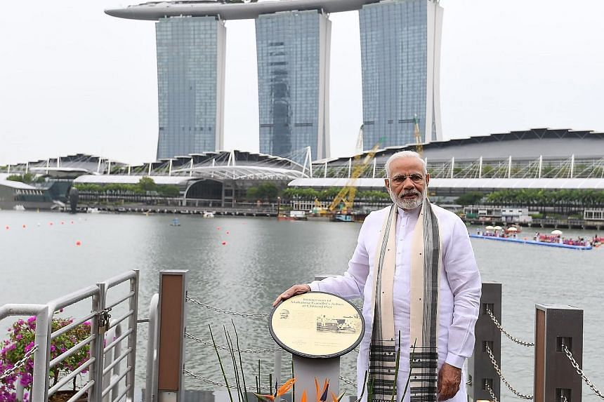 Indian Prime Minister Narendra Modi with Minister for Culture, Community and Youth Grace Fu at the Buddha Tooth Relic Temple and Museum (right) in South Bridge Road yesterday. He also unveiled a plaque (far right, above) at Clifford Pier, marking the