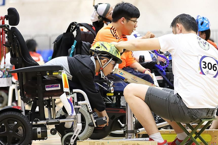 Aloysius Gan, 11, preparing to release the boccia ball in a BC3 pairs match at the Tiger Balm Singapore Boccia Open yesterday. With him is his father and ramp assistant Kagan Gan. Aloysius and partner Toh Sze Ning won the pairs silver medal.