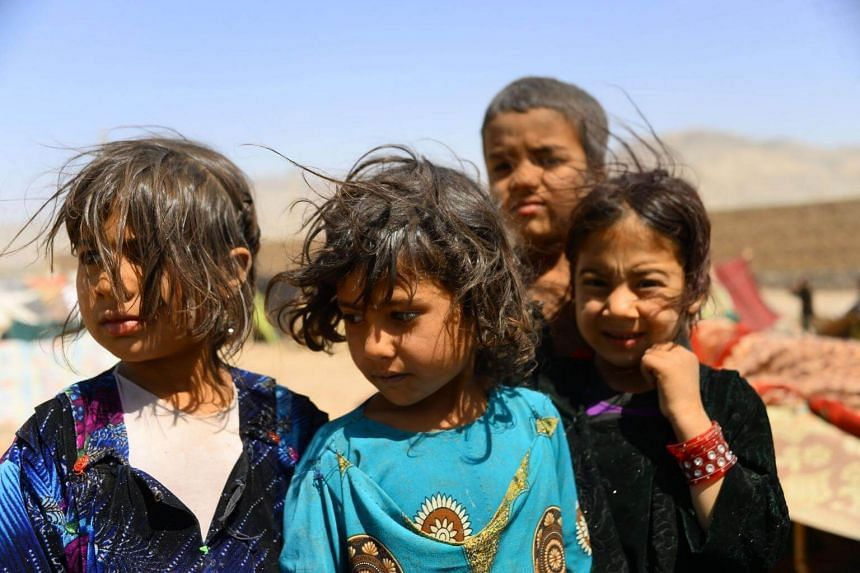 Afghan children waiting outside their temporary house at a refugee camp on the outskirts of Herat, on May 30, 2018.