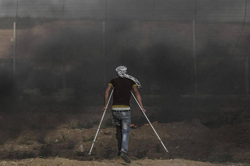 An injured Palestinian protester takes part during clashes near the border between Israel and the Gaza Strip, in eastern Gaza City, on June 1, 2018.