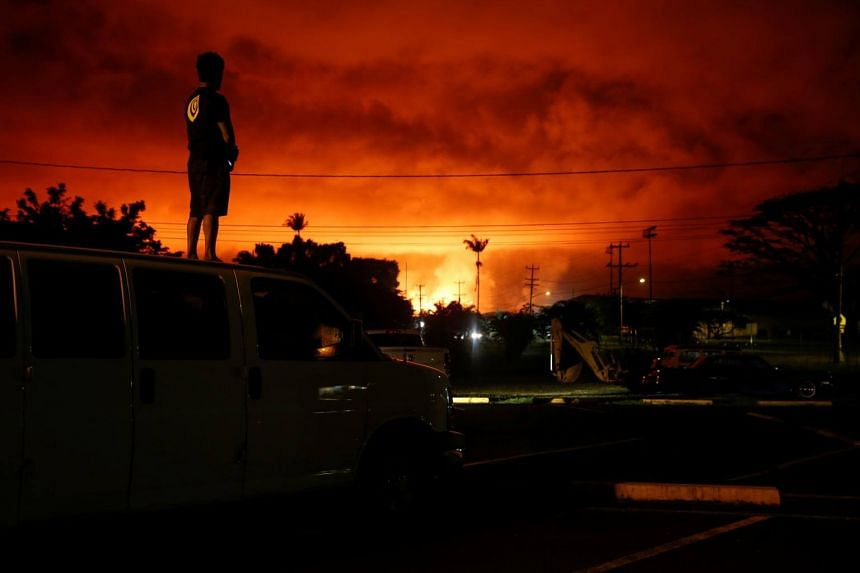 A resident watching as lava lights up the sky above Pahoa, Hawaii, during ongoing eruptions, on June 2, 2018.