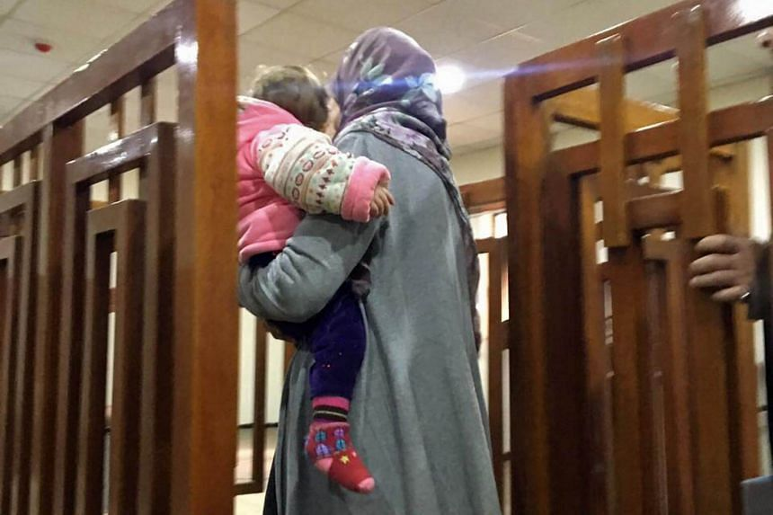 Melina Boughedir, who is carriyng her son, arriving in court in the Iraqi capital Baghdad on Feb 19, 2018.