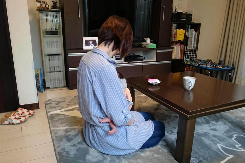 Sayako, who spoke to reporters using a pseudonym, holding her baby during an interview in Tokyo, on April 23, 2018.