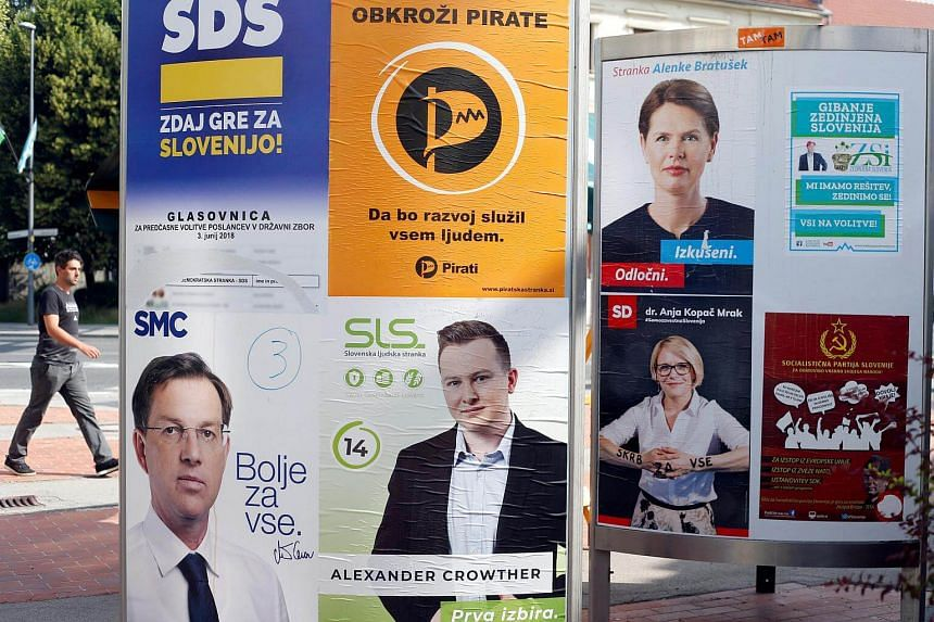 A man walks next to election posters for general elections in Ljubljana, Slovenia, on May 31, 2018.