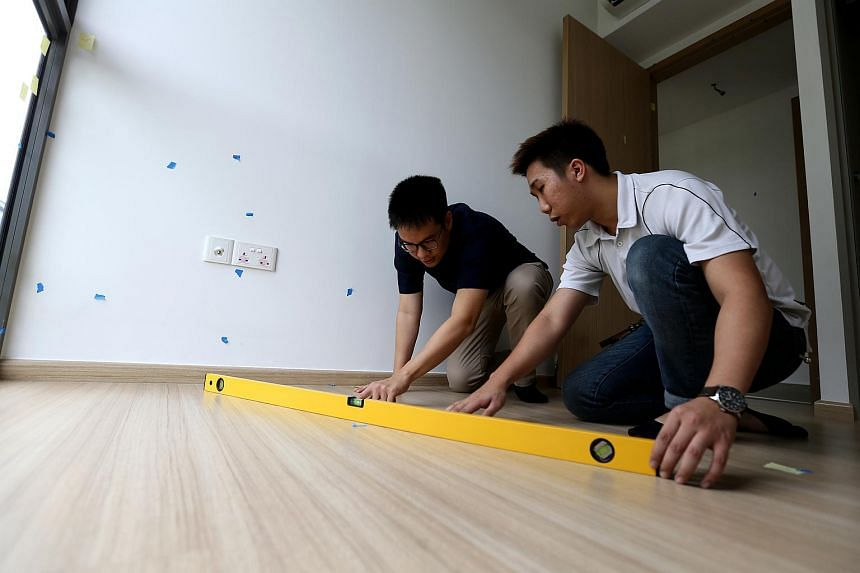 Lead inspector Joelson Sim (right) showing ST reporter Derek Wong the inspection process with the use of a spirit level.