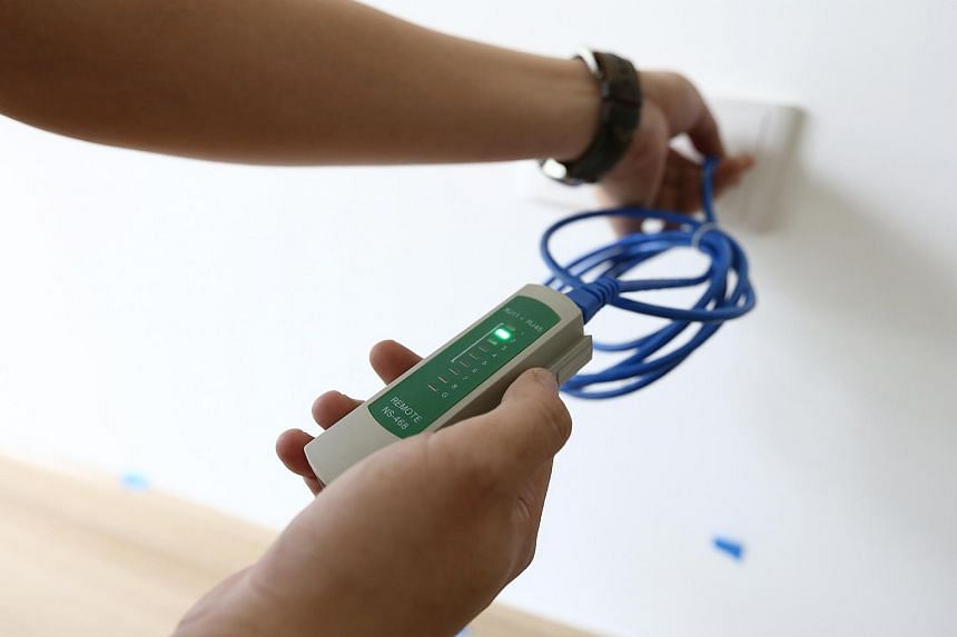 Mr Sim using a network cable tester to check if the data point in the home is working.