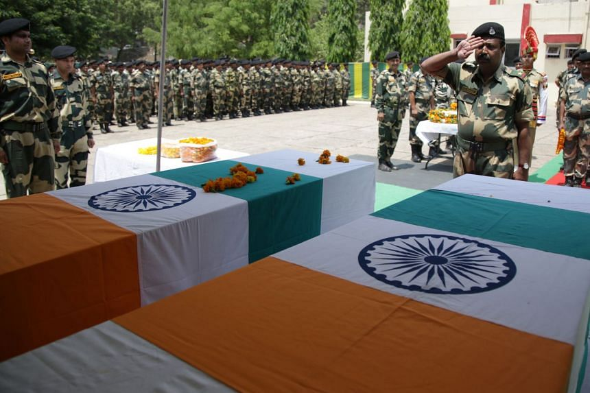 An Indian Border Security Force officer salutes the coffins of two soldiers who were killed in alleged firing from the Pakistani side in Akhnoor sector, Kashmir, on June 3, 2018.