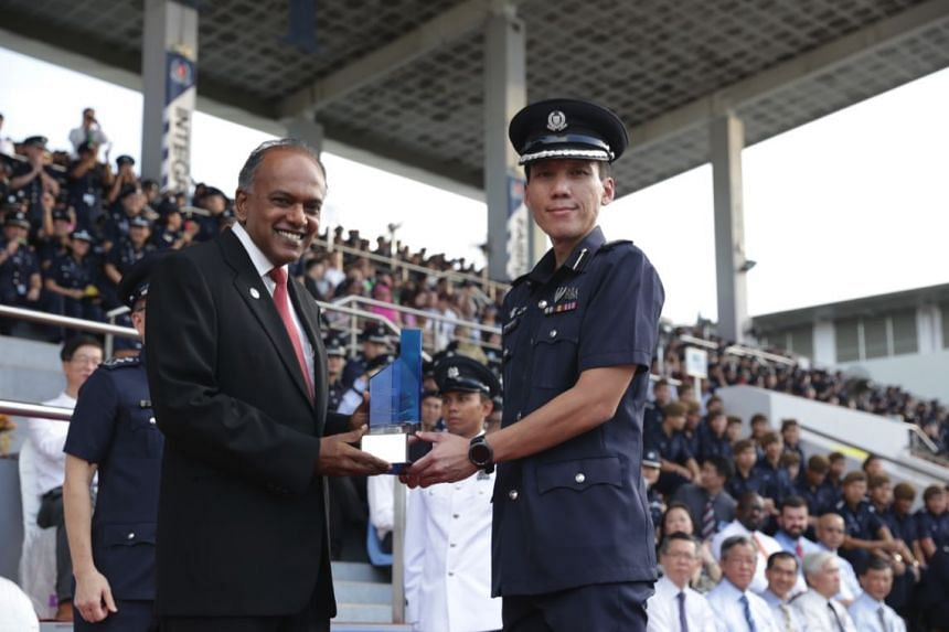 Home Affairs Minister K Shanmugam giving the Best Land Division award to Central Division commander Arthur Law.