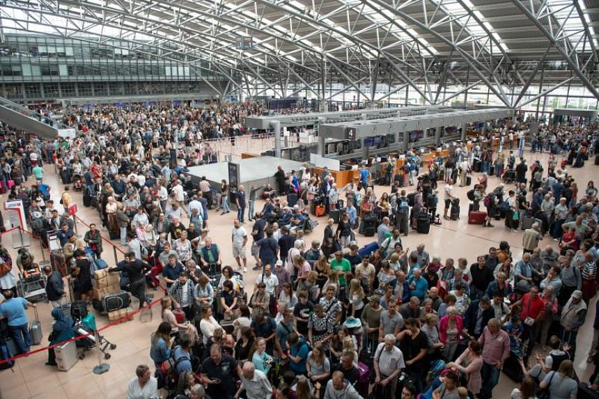 Travellers wait at Hamburg airport on June 3, 2018 as Germany's fifth busiest, ground to a halt due to a power outage caused by a short circuit.