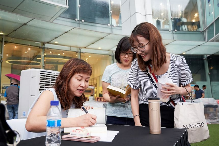 Ms Lorna Tan signing books (above) at the session on May 26, where she spoke on financial and retirement planning.