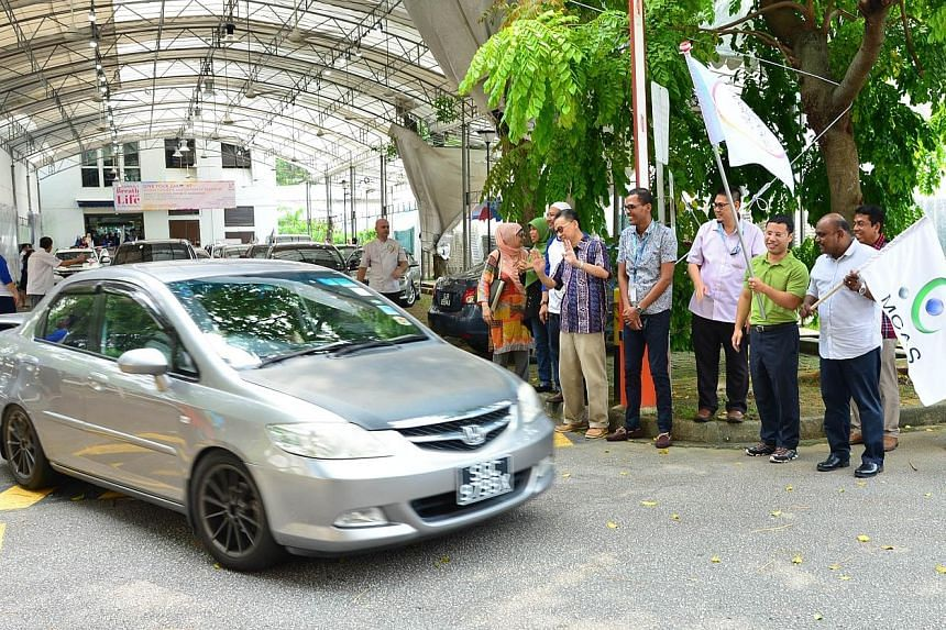 Minister for Social and Family Development, Mr Desmond Lee (in green), flagging off cars at yesterday's Meals On Wheels event organised by Darul Arqam Singapore, also known as the Muslim Converts' Association of Singapore (MCAS). With him, holding th