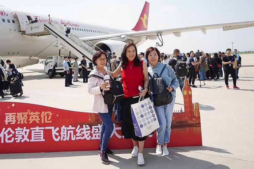 Passengers posing for photos before boarding a direct flight from Xi'an's airport to London on May 7. The new service by Tianjin Airlines cuts the journey from 15-plus hours to around 11 hours.