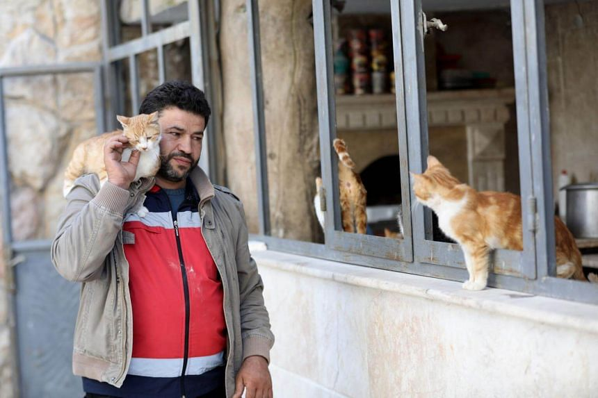 Mohammed Alaa al-Jaleel carries a cat on his shoulder at Ernesto's Cat Sanctuary that he runs in Kfar Naha, an opposition-held town in Aleppo province in Syria, on March 17, 2018.