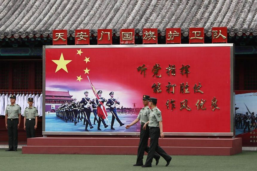 Chinese People's Liberation Army soldiers walk past a wall mural for the Tiananmen Flag Defence division inside the grounds of the Forbidden City across Tiananmen Square in Beijing, China, on June 3, 2018.