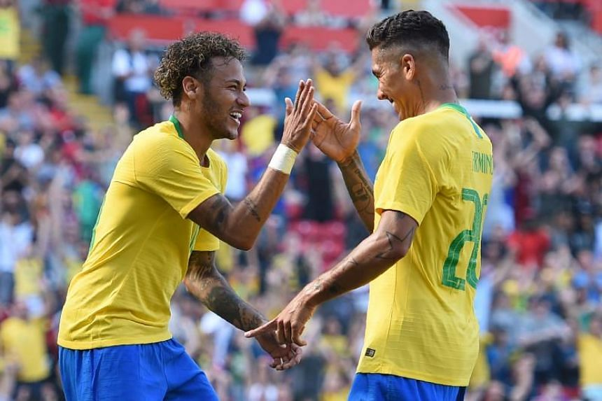 Brazil's striker Roberto Firmino (right) celebrates with Brazil's striker Neymar after scoring their second goal during the International friendly football match between Brazil and Croatia at Anfield in Liverpool on June 3, 2018.