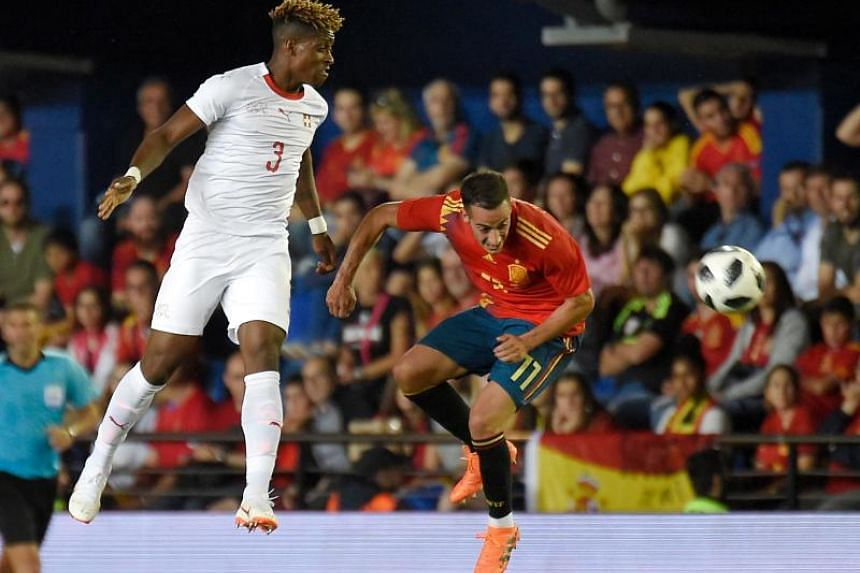 Switzerland's defender Francois Moubandje (left) vies with Spain's forward Lucas Vazquez during the international friendly football match between Spain and Switzerland at La Ceramica stadium in Vila-real, on June 3, 2018.